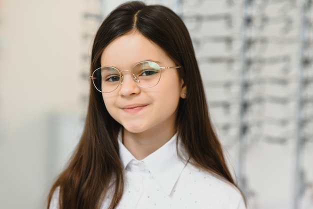 Cute little girl with new glasses in shop