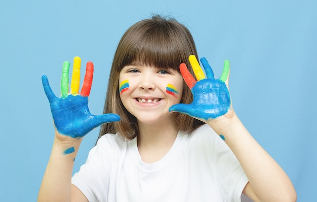 Cute little girl with painted hands. isolated on blue background.