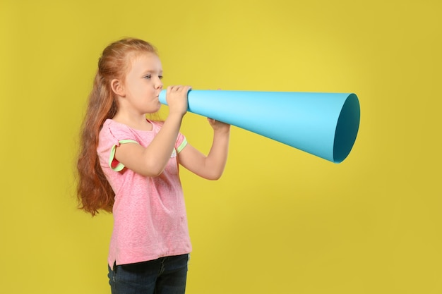 Cute little girl with paper megaphone on color