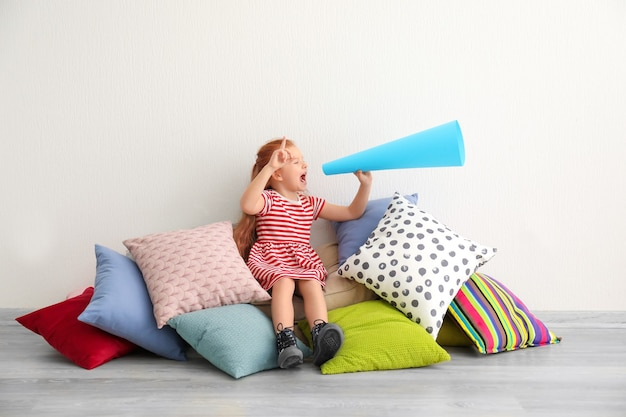 Cute little girl with paper megaphone on pile of pillows indoors