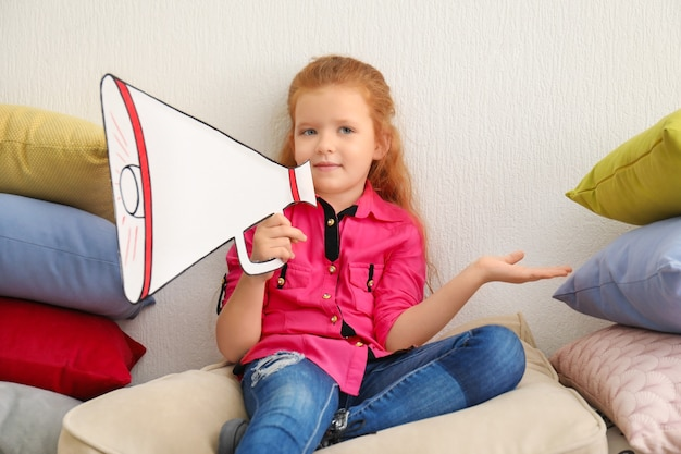 Cute little girl with paper megaphone sitting among pile of pillows indoors