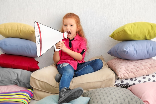 Cute little girl with paper megaphone sitting on pile of pillows indoors