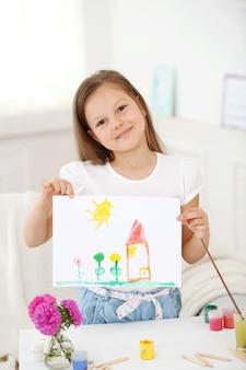 Милая маленькая девочка с изображением на фоне домашнего интерьера