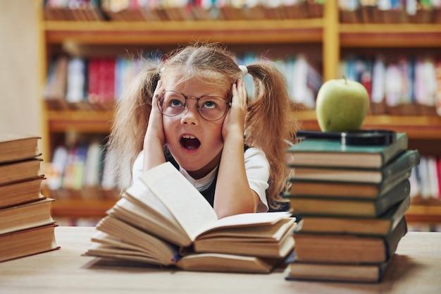 Милая маленькая девочка с косичками находится в библиотеке