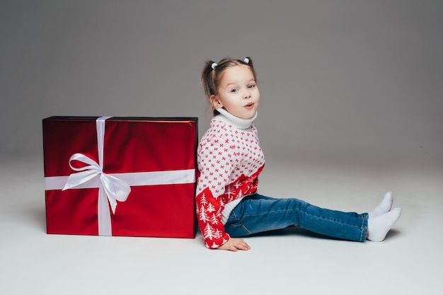 Cute little girl with ponytails in winter sweater and jeans sitting back to red wrapped christmas present with white bow. kid pouting lips at camera.