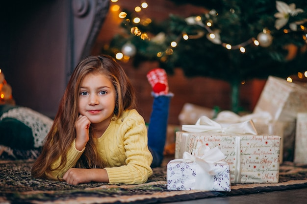Cute little girl with presents by the christmas tree