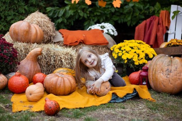 Cute little girl with pumpkin outdoors
