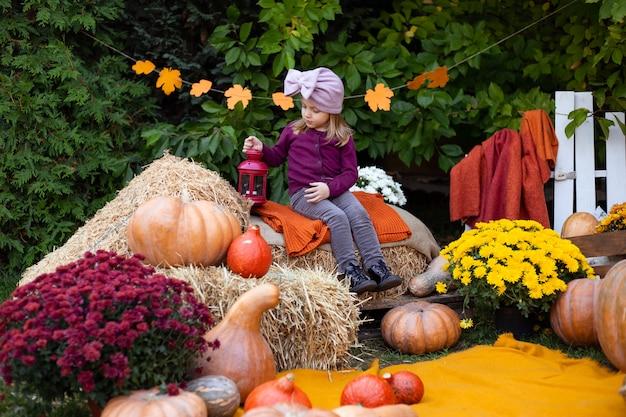 Cute little girl with pumpkins outdoor