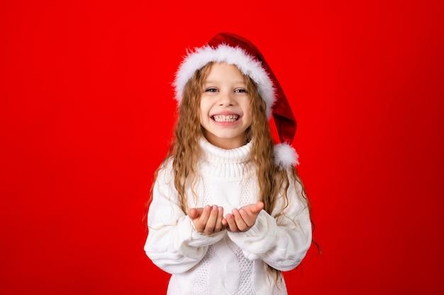 サンタの帽子とセーターを持ったかわいい女の子