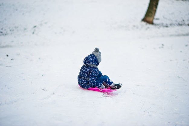 Cute little girl with saucer sleds outdoors on winter day.