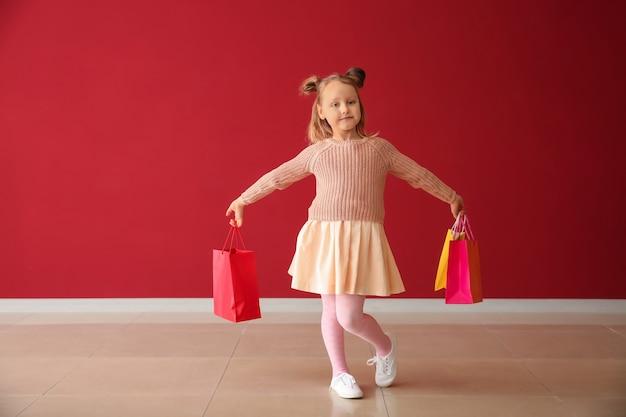 Милая маленькая девочка с хозяйственными сумками возле цветной стены
