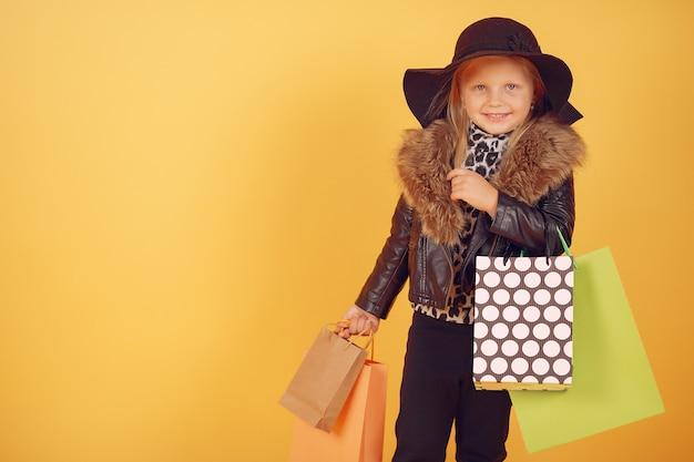 黄色の背景に買い物袋を持つかわいい女の子