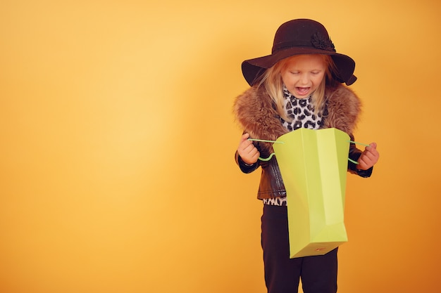 Cute little girl with shopping bags on a yellow background