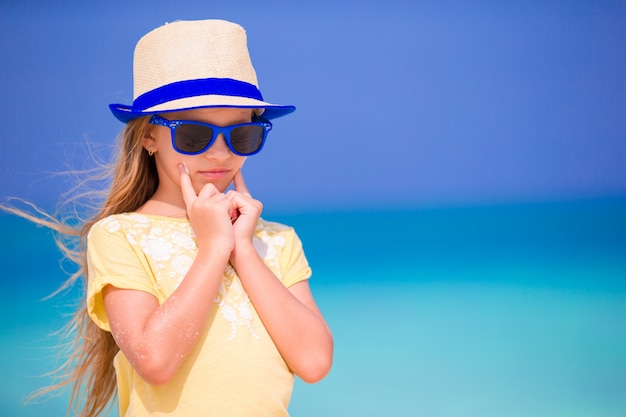 Cute little girl with suncream at beach during summer vacation