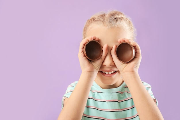 Милая маленькая девочка со сладким шоколадным яйцом на цветной поверхности