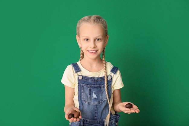 Милая маленькая девочка со сладкими шоколадными яйцами на цвете