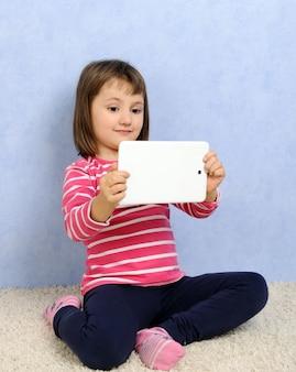 Милая маленькая девочка с планшетом