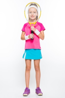 Cute little girl with tennis racket in front of her head on white wall