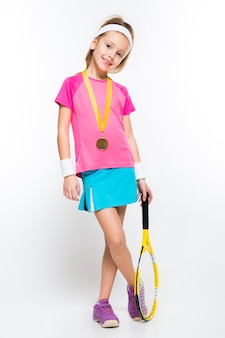 Cute little girl with tennis racket and medal in her hands