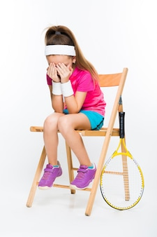Cute little girl with tennis racket on white