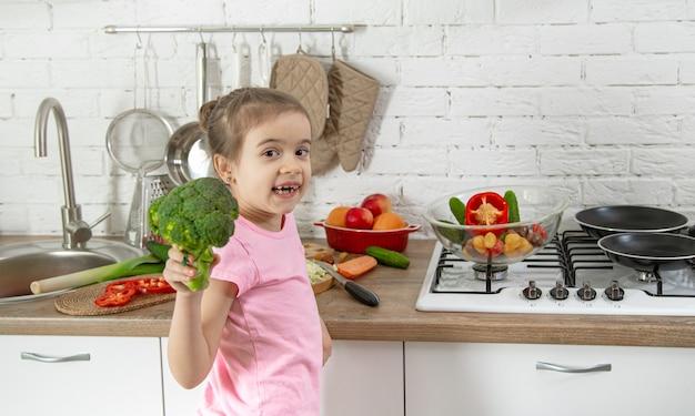 台所で野菜とかわいい女の子。健康的な食事とライフスタイルのコンセプト。家族の価値。