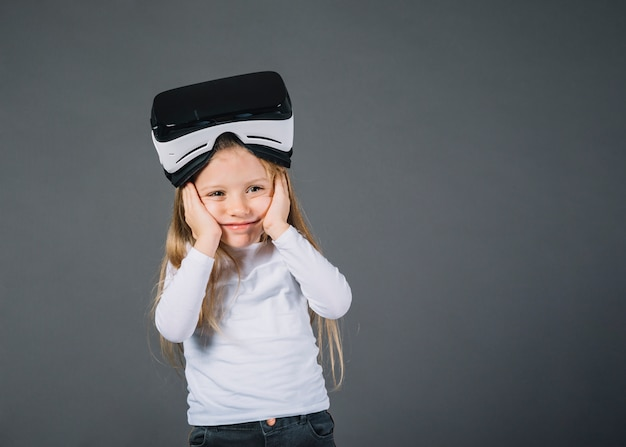 Cute little girl with virtual reality glasses on head holding her cheeks