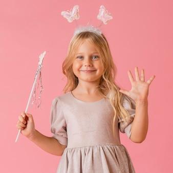 Милая маленькая девочка с палочкой в костюме