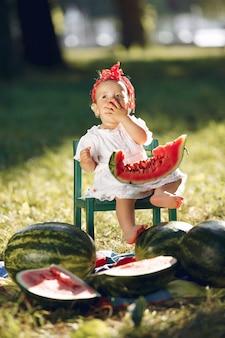 Милая маленькая девочка с арбузами в парке