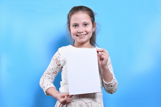Cute little girl with white hair holds a book with white siege.