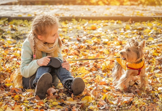 Милая маленькая девочка с йоркширским терьером в осеннем парке