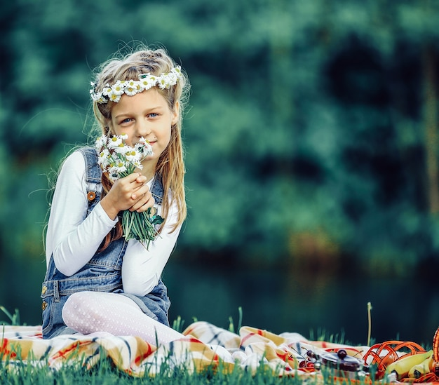 Cute little girl in a wreath and a bouquet of wildflowers on a picnic in the woods
