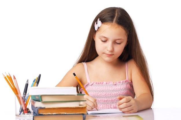 연필과 책 근처 카피 북에서 뭔가 쓰는 귀여운 소녀.