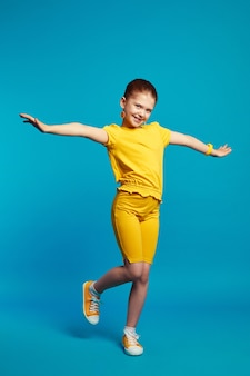 Cute little girl in yellow outfit smiling and dancing against blue
