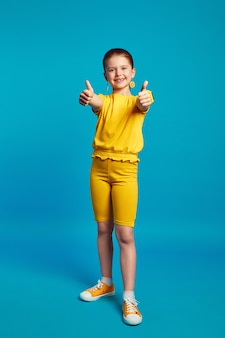Cute little girl in yellow outfit smiling and showing thumbs up against