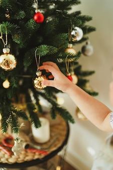 귀여운 소녀는 금색과 가장자리 공과 빛나는 화환으로 현대적인 크리스마스 트리를 장식합니다. 새 해와 크리스마스 축 하 개념입니다. 세련된 최소한의 구성.