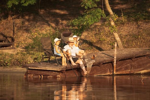 かわいい女の子とそのおじいちゃんは、湖や川で釣りをしています。夏の日の入り時間に水と森の近くの桟橋で休んでいます。家族、レクリエーション、子供時代、自然の概念。