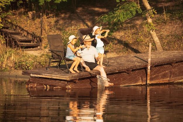 Симпатичные маленькие девочки и их дедушка на рыбалке на озере или реке