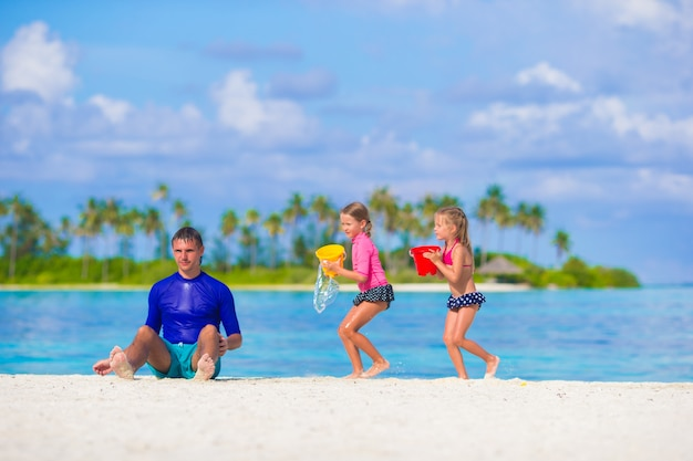 Cute little girls and father having fun with beach toys on summer vacation