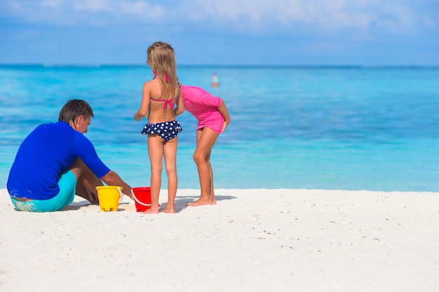 Cute little girls having fun with dad on white beach
