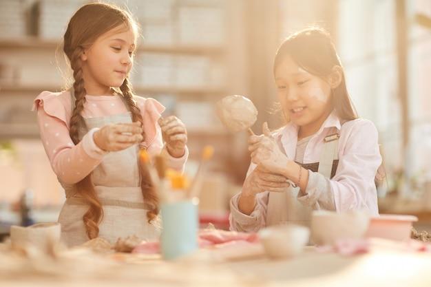 Симпатичные маленькие девочки в классе керамики