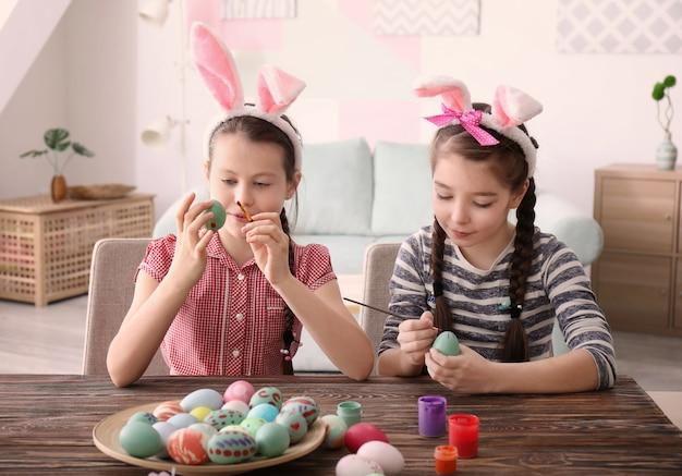 Симпатичные маленькие девочки красят яйца на пасху за столом