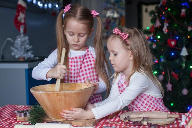 Cute little girls preparing gingerbread cookies for christmas