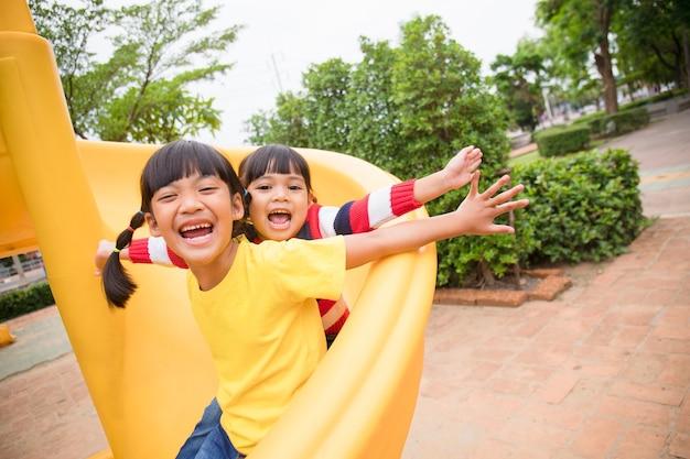 晴れた夏の日に屋外の遊び場で楽しんでいるかわいい女の子の兄弟。プラスチック製のスライド上の子供たち。子供のための楽しい活動。子供のためのアクティブなスポーツレジャー
