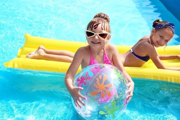Cute little girls in swimming pool on summer day