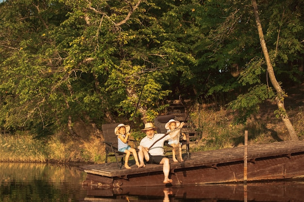Bambine sveglie e il loro nonno pescano al lago o al fiume