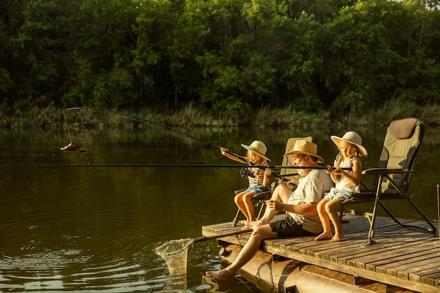 Cute little girls and their granddad are on fishing at the lake or river