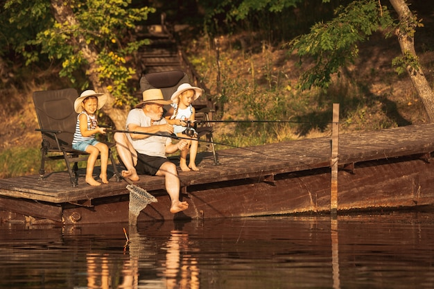 Cute little girls and their granddad are on fishing at the lake or river.