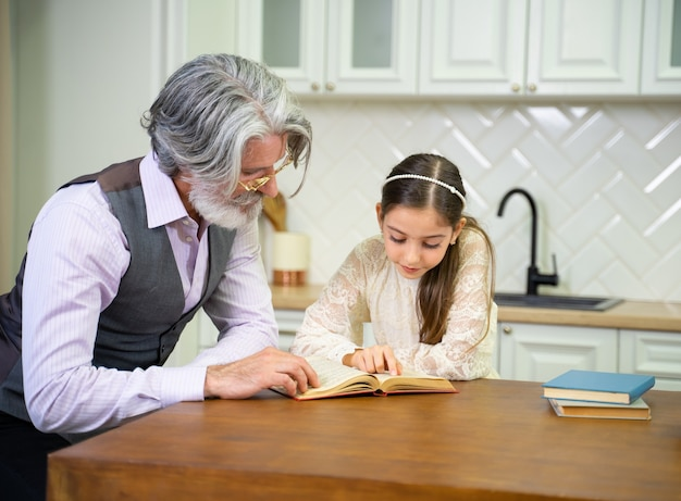 Cute little granddaughter reading story book with  grandfather  while sitting in the kitchen