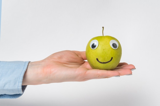 Cute little green apple with googly eyes and smile rests in palm. white background