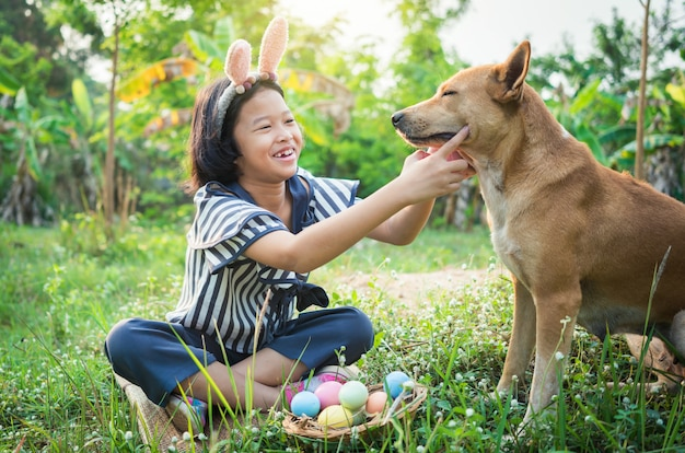 Cute little gril wearing bunny ears with easter eggs and dog.